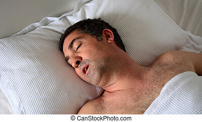 Man snoring in bed - Man in his forties (40s) snoring in...