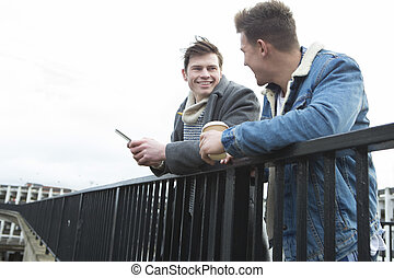 Two men talking in the city - Two young men talking in the...
