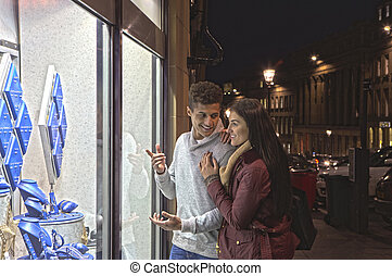 Young couple looking at jewellery through a shop window in...