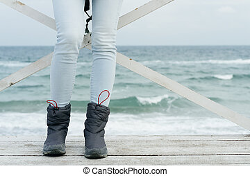 Female feet in jeans and sports boots on wooden boards against the sea close-up
