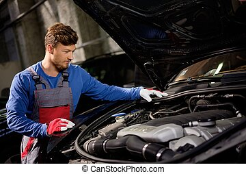 Mechanic checking under hood in a workshop