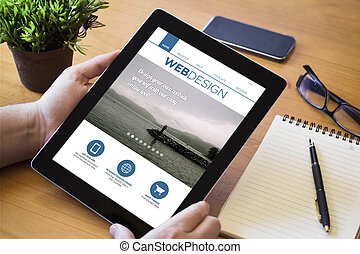desktop tablet web design - hands of a man holding a web...