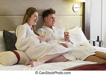 Couple enjoying a drink in hotel room