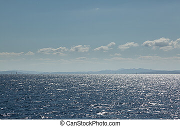 Coastline of Sardinia with several sailing boats in sunshine...