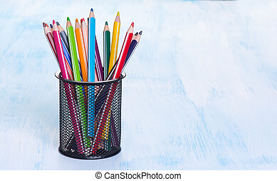 Colour pencils in a black mug on blue background