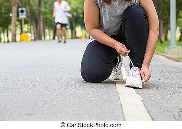 Woman tying shoe laces
