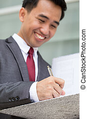 Asian businessman signing a document