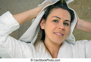 Young woman wiping wet hair with a towel - Closeup of...