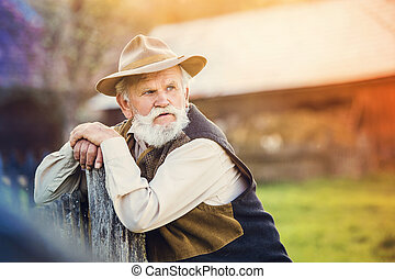 Senior man outside - Senior man standing outside at the...
