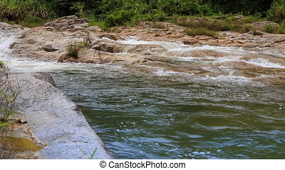 mountain stream flows along plane surface in park - mountain...
