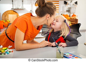 Mother with halloween dressed daughter in decorated kitchen...