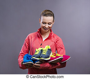 Beautiful young sportswoman. Studio shot on gray background.