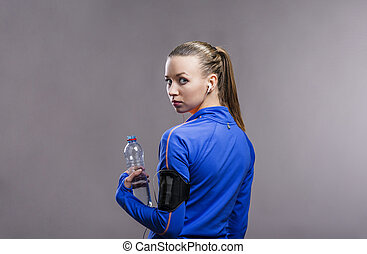 Beautiful young sportswoman Studio shot on gray background