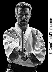 low key portrait of aikido master with wooden sword