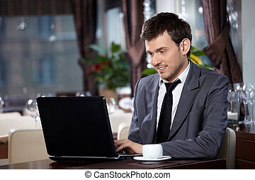 Professional - Business man with the laptop sits at a table...