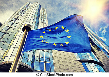 EU flag waving in front of European Parliament building in Brussels
