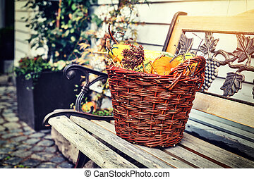 Woven basket with small pumpkins. Outdoor decoration
