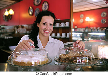 waitress of a pastry store showing tasty cakes