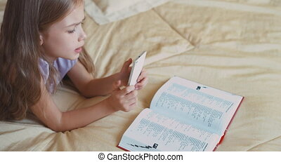 Schoolgirl Child girl using cell phone on the bed and...
