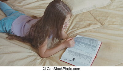 Child girl reading a book lying on the bed and smiling at camera. Top view