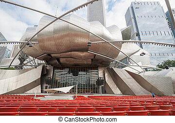 Jay Prtizker Pavilion in  Chicago Millennium Park, designed by Frank Gehry, surrounded by highrise commercial buildings, Illinois, USA