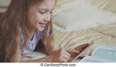 Schoolgirl Child girl using smartphone cell phone and lying on the bed and smiling at camera