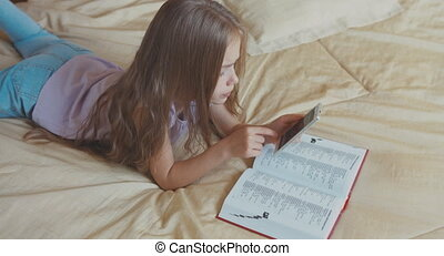 Child girl reading a book lying on the bed and looking at camera. Top view