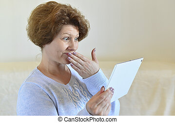 woman in amazement looking at tablet computer