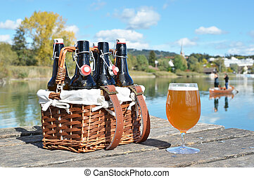 Beer bottles in the vintage basket on a wooden pier