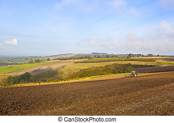 yorkshire wolds farming - a red tractor plowing a field in...
