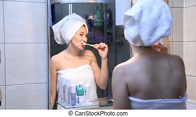 woman brushing her teeth in front of mirror