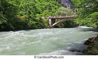 Running water at the mountain river with bridge on...