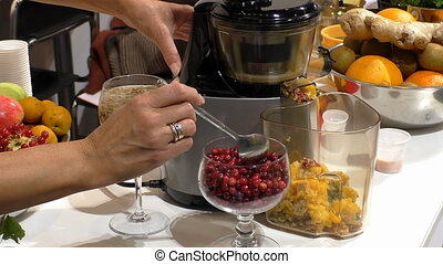 Juice maker - Woman puts some cranberries into working...