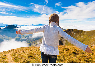 Portrait of a cute little girl in mountains, wearing grey pullover, arms wide open, back view, Moleson-sur-Gruyeres, canton of Fribourg, Switzerland