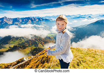 Portrait of a cute little girl in mountains, wearing grey pullover, Moleson-sur-Gruyeres, canton of Fribourg, Switzerland