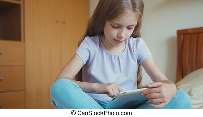 Portrait schoolgirl using tablet pc in the bedroom. Child 6-8 years sitting on the bed and laughing