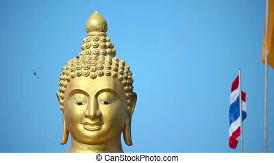 Buddha gold statue on blue sky background - Buddha gold...