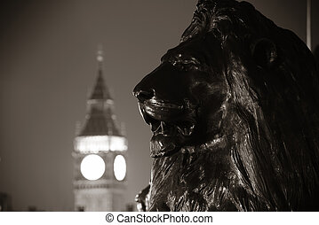 Trafalgar Square lion statue and Big Ben in London at night...