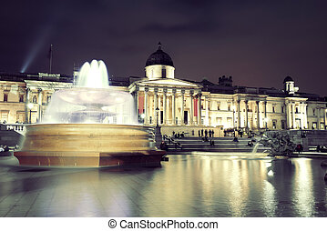 Trafalgar Square at night with fountain and national gallery...