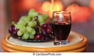 Plate with grapes and glass of wine on fireplace background
