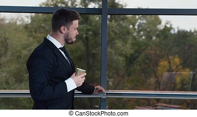 Young businessman drinking coffee at office window