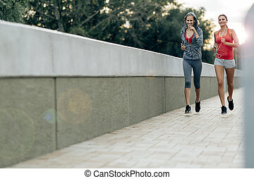 Active female joggers running outdoors and listening to...