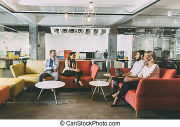 Group of young people talking in modern cafe