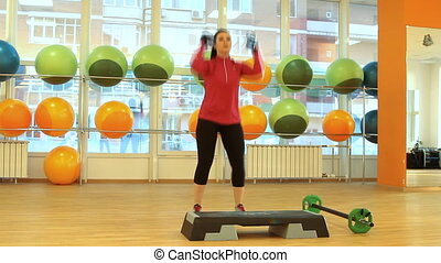 Young woman doing exercise with dumbbells - Young woman...