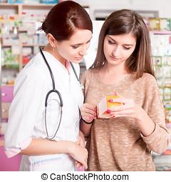 Pharmacist and customer looking at medication box