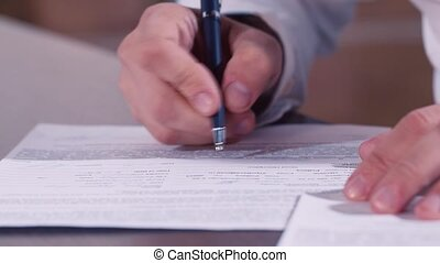 Mans hand writing text in documents