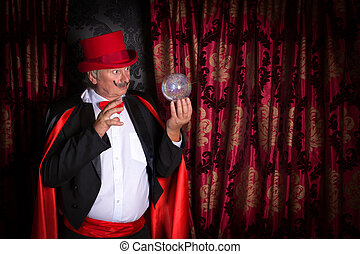 Crystal ball magician - Senior magician performing on stage...