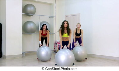 Fitness. Aerobics with the fitballs - Young women doing...