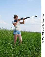 Girl with air rifle - The woman aiming a pneumatic air rifle