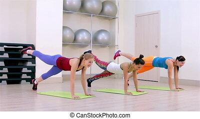 Fitness Aerobics on the floor - Young women doing aerobics...